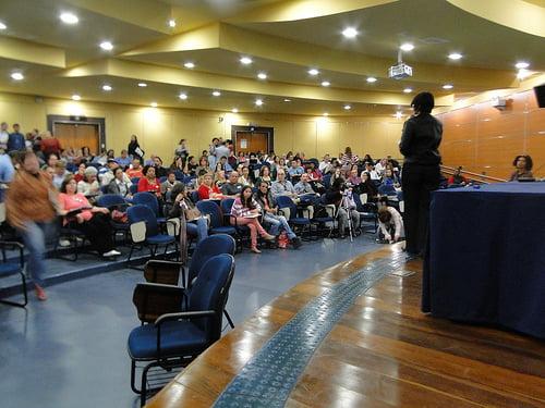 A imagem mostra um palestrante conversando com um auditório cheio.