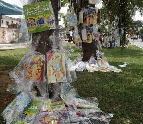 Foto da 7ª edição do festival, Clube da Comunidade Tide Setúbal, mostra um parque, com árvores, e livros pendurados em seus troncos.