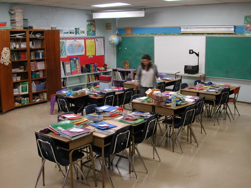 Imagem de uma sala de aula com as carteiras escolares juntas e livros.