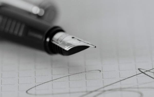 Imagem de uma caneta em cima de uma folha de papel.