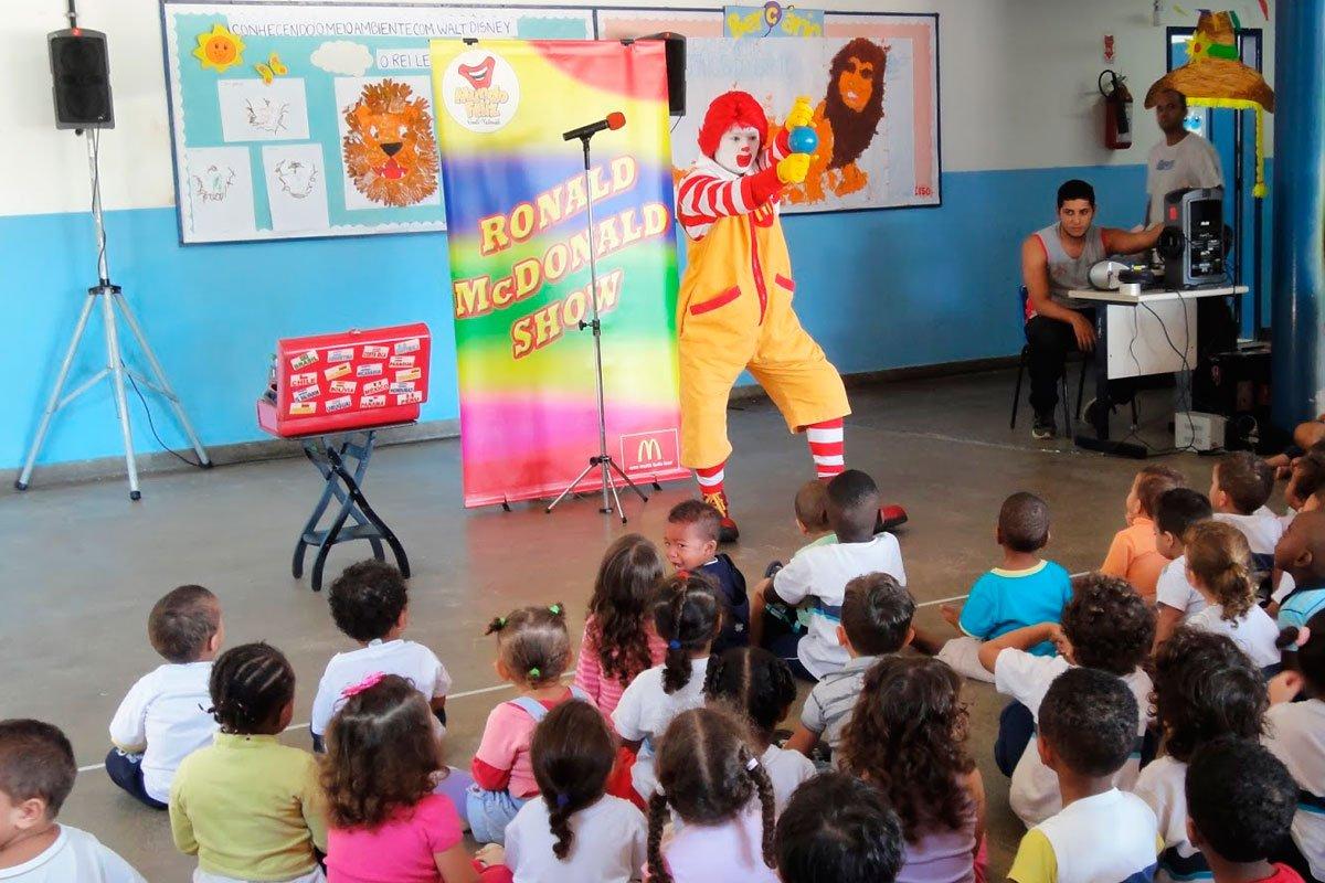 Crianças vendo um show do Ronald Mc Donalds em uma escola.
