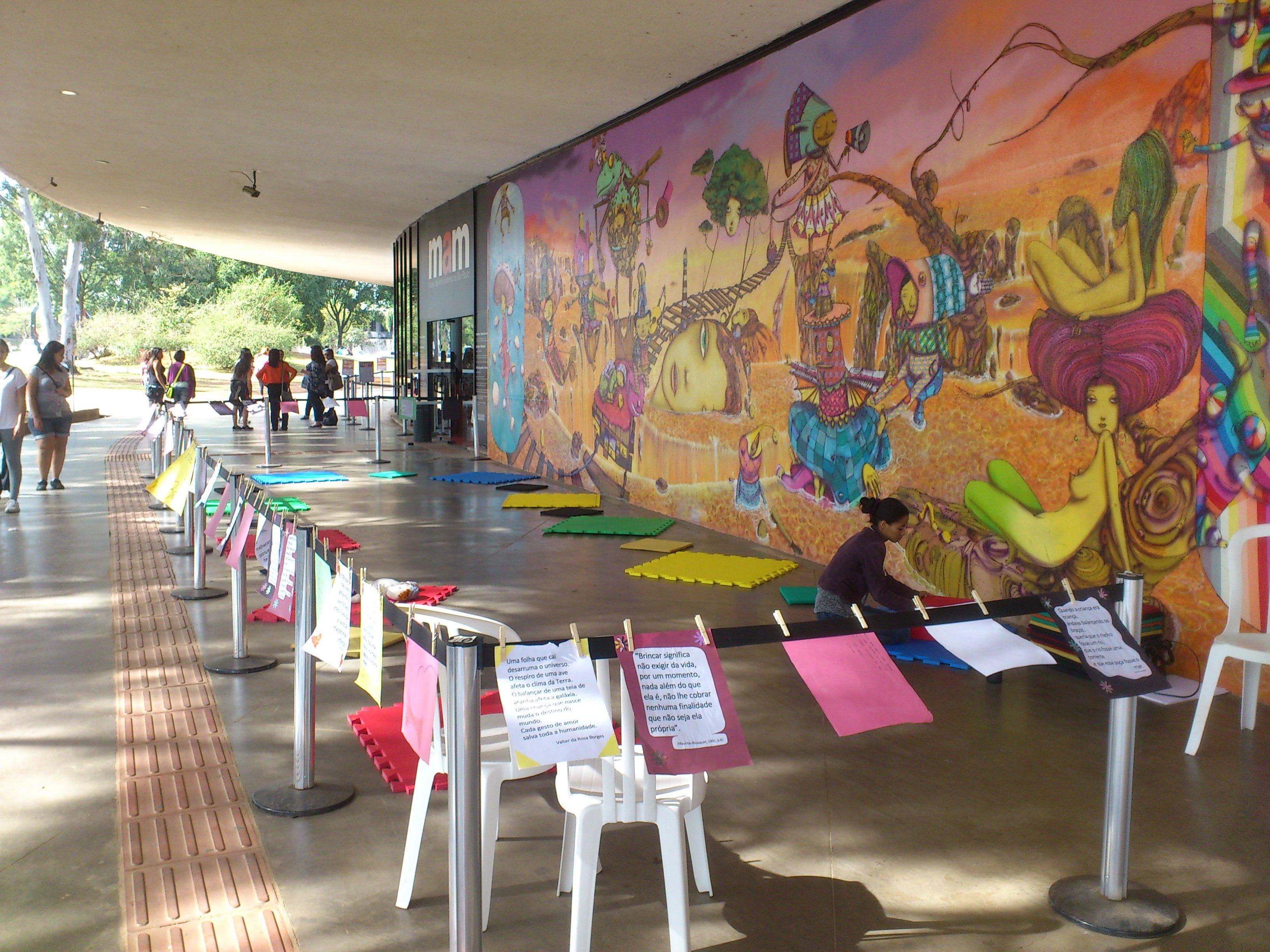 Espaço reservado para crianças, com tapetes coloridos no chão, e folhas coloridas penduradas em um cercado.