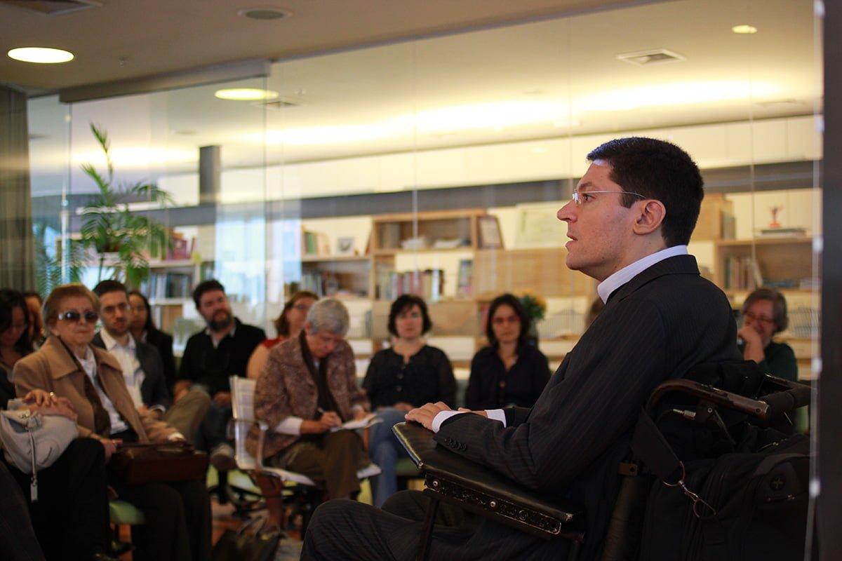 Perfil de um homem dando uma palestra. Ao fundo pessoas o assistem.