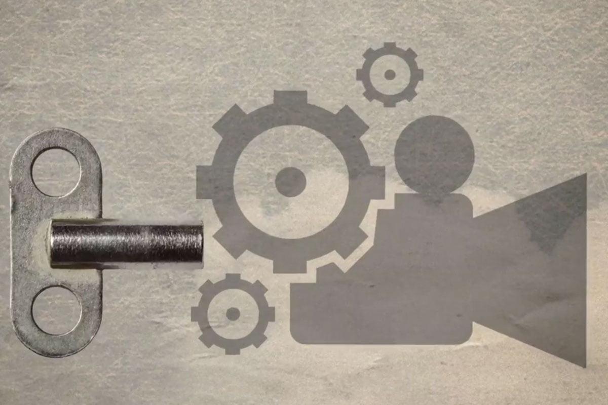 Desenho cinza, de uma câmera sendo desmontada por uma chave de dar corda.