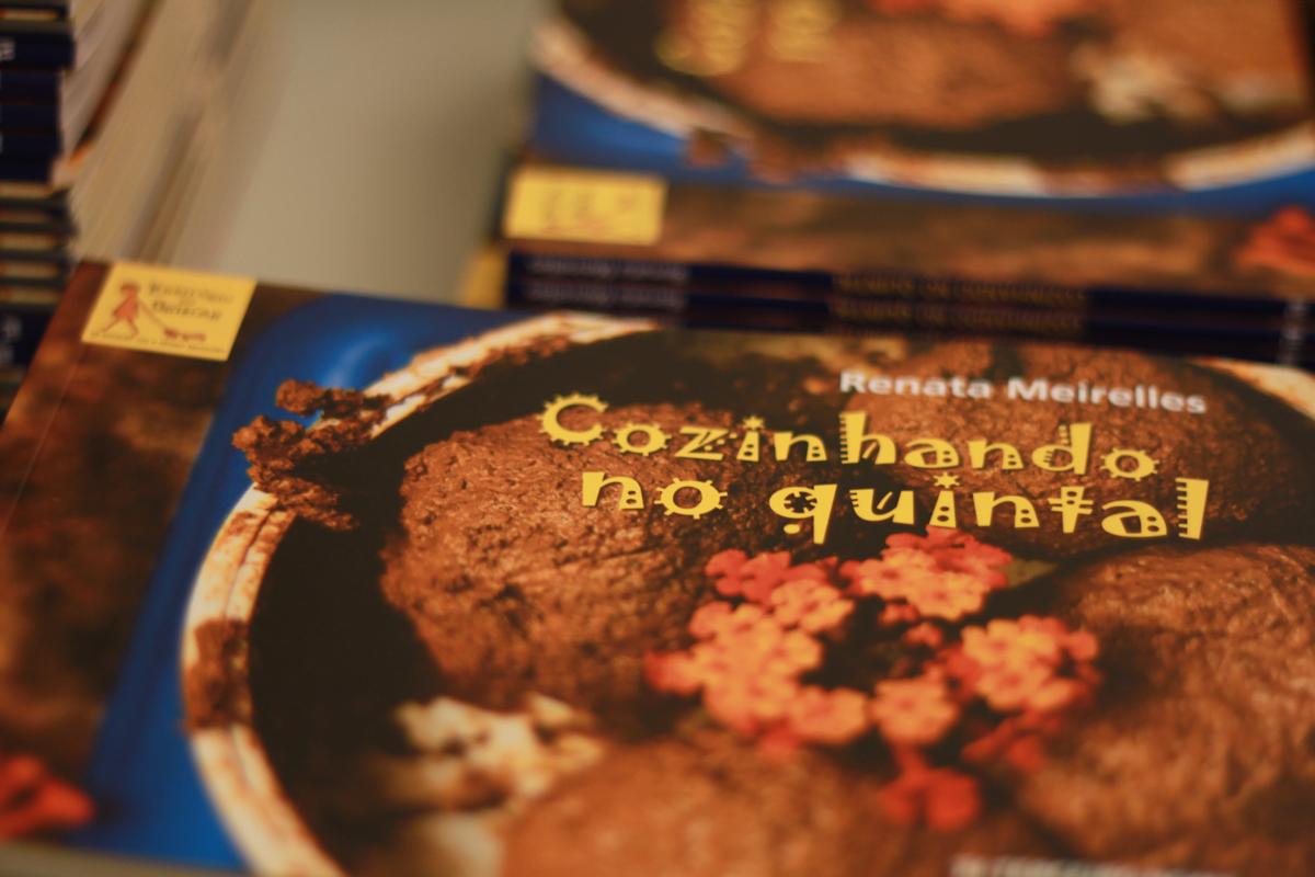 Foto da capa do livro Cozinhando no Quintal, com letras em amarelo em cima da foto de lama moldada com flores.