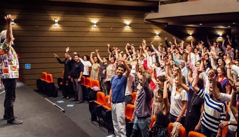 Imagem mostra plateia de um auditório, com pessoa de pé e com uma das mãos levantadas.