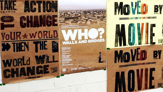 """Posters com os dizeres """" Take action to change your world"""", """"Who? Walls and bridges"""" e """"Moved by movie""""."""