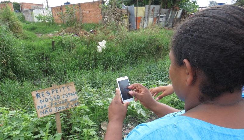 """Foto de mulher tirando foto com o celular de uma placa escrito """"Respeite nosso espaço, por favor, não jogue lixo""""."""