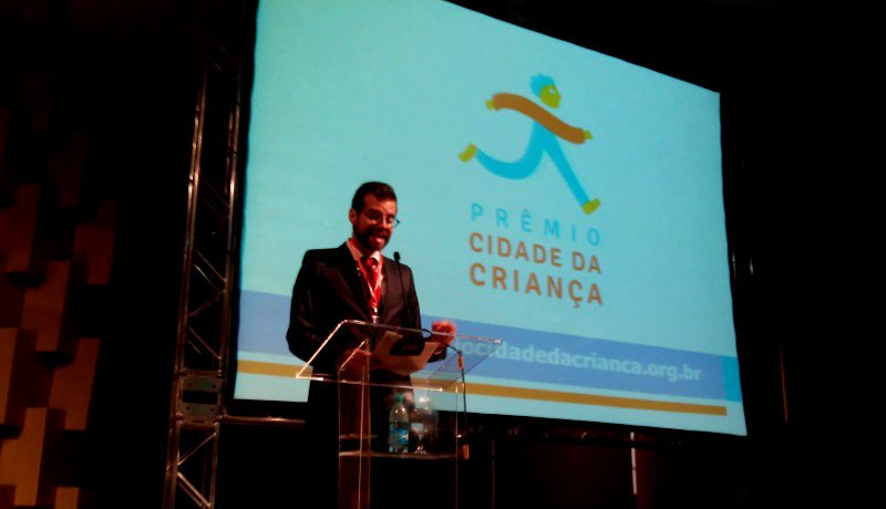 Pedro Hartung falando ao microfone atrás de um púlpito transparente. Atrás, um telão com o texto: Prêmio Cidade da Criança