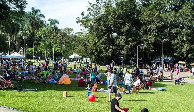 Parque com uma extensa área de gramado verde e pessoas circulando pelo local.