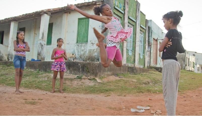 Foto de quatro meninas negras brincando de pular corda em rua de terra