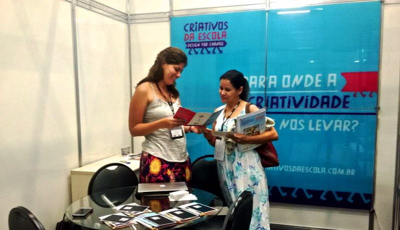 Mulheres em pé em frente a um banner do Criativos da Escola, conversando e vendo um livro.