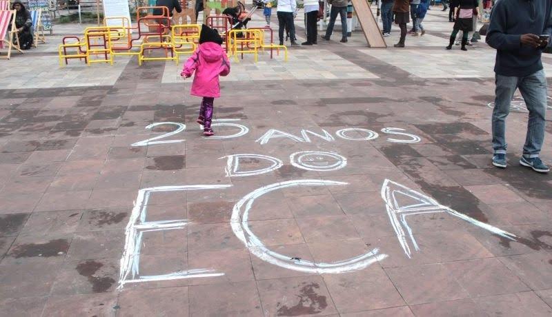 """Chão riscado de giz branco, com frase """"25 anos do ECA"""". Ao fundo criança aparece pulando."""