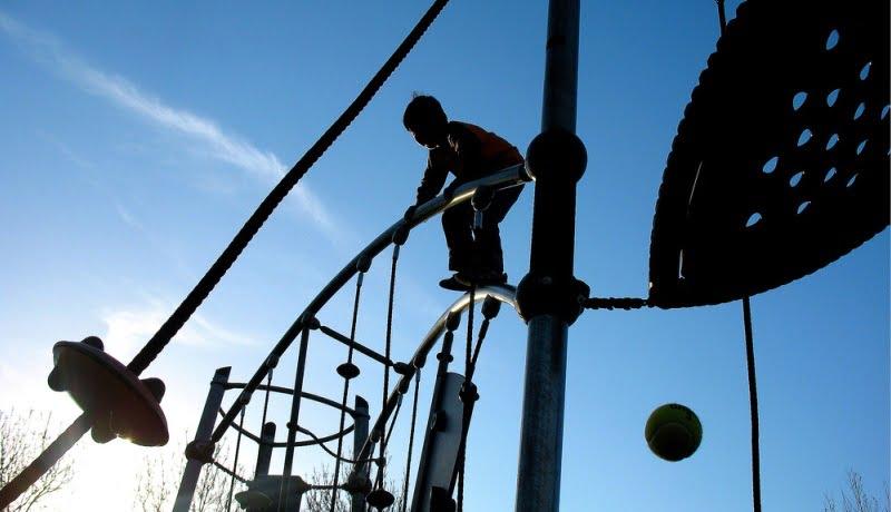 Imagem feita de baixo mostra sombra de uma criança em cima de um brinquedo.