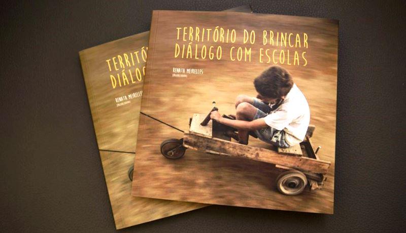 """Capa do livro """"Território do Brincar, diálogo com escolas"""" com um menino brincando com um carrinho de rolimã"""