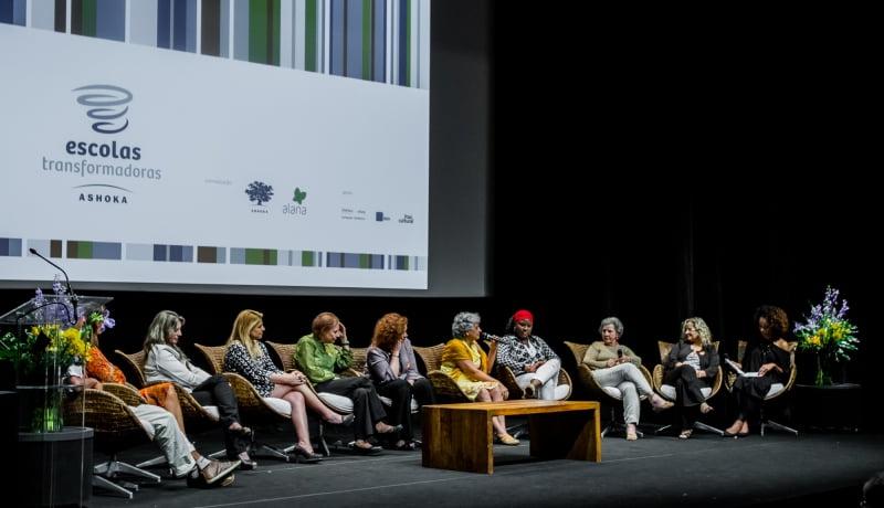 Pessoas sentadas em um palco. Atrás delas, aparece um telão multimídia.