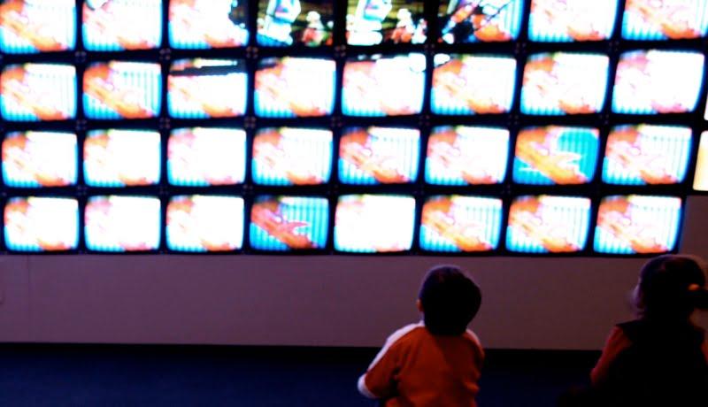 Crianças em frente a diversas telas de televisão