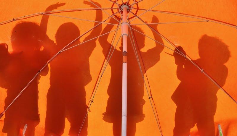 Educação integral. Sombras de crianças sendo refletidas em um fundo laranja.