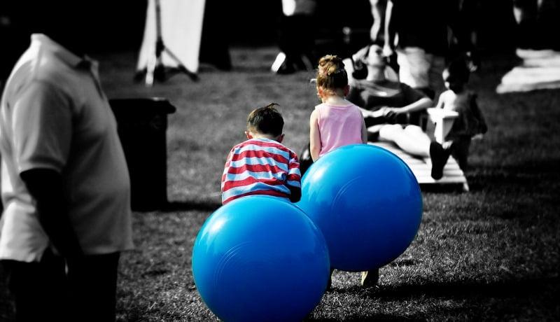 Duas crianças sentadas em bolas de ar azul, brincando no meio da cidade.