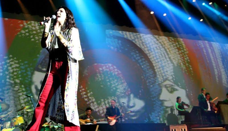 Show com luzes azuis, e uma cantora no canto esquerdo da imagem.