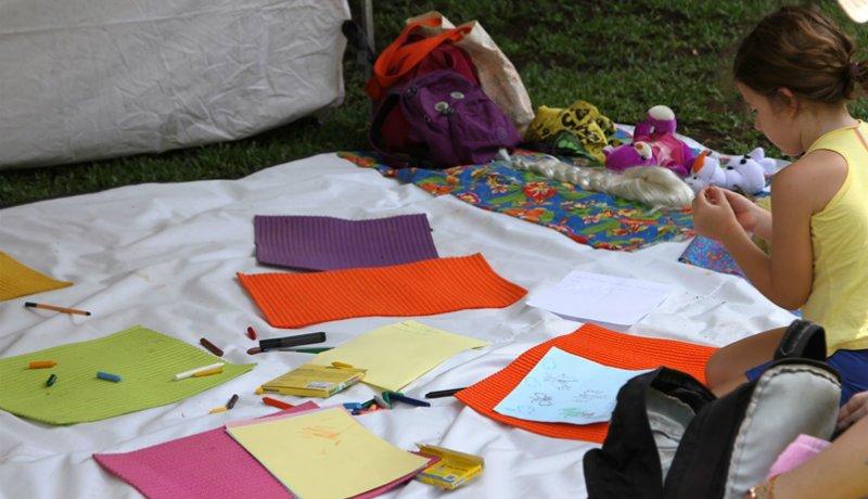 Pano branco com diversos papéis coloridos em cima, e uma criança desenhando.