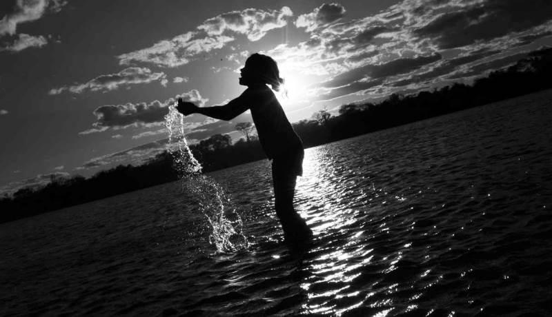 Criança brincando em um rio, no fundo o brilho do sol.