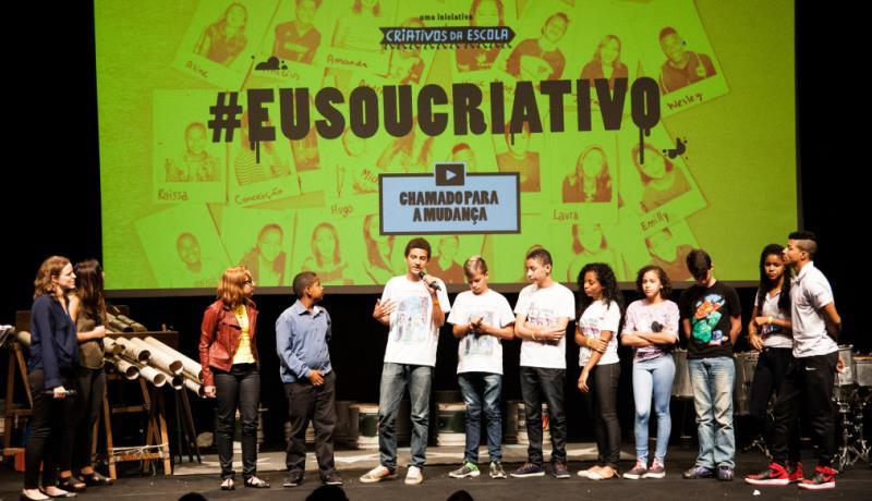Foto mostra vencedores do Desafio Criativos da Escola apresentando o projeto. No fundo um telão escrito #eusoucriativo.