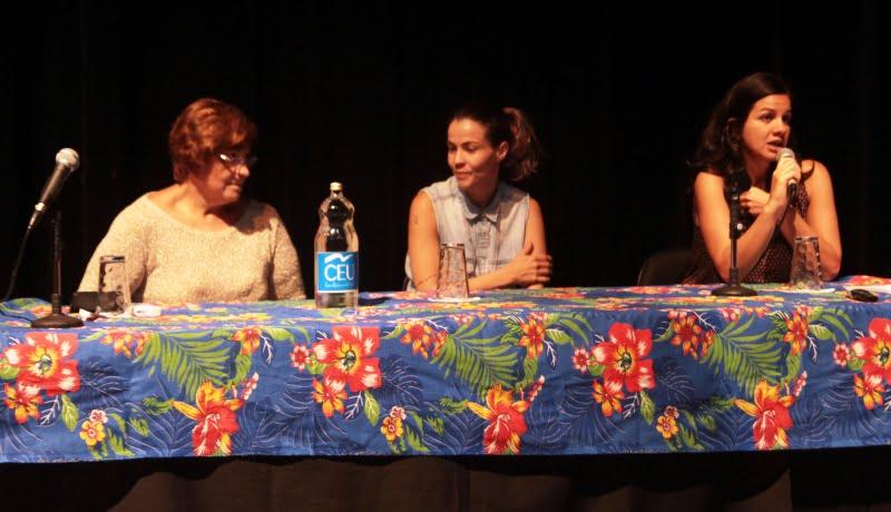 Foto do evento mostra mesa com toalha estampada em chita, e participantes do evento sentadas de frente pro auditório.
