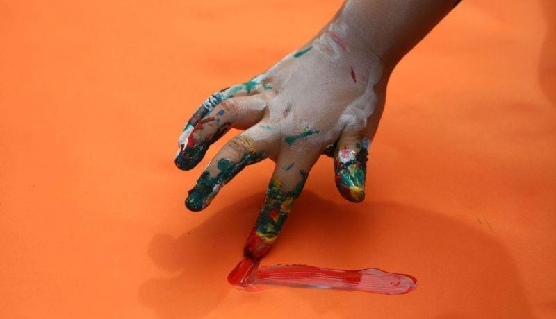 Mão fazendo um risco vermelho de tinta, em cima de um papel laranja.