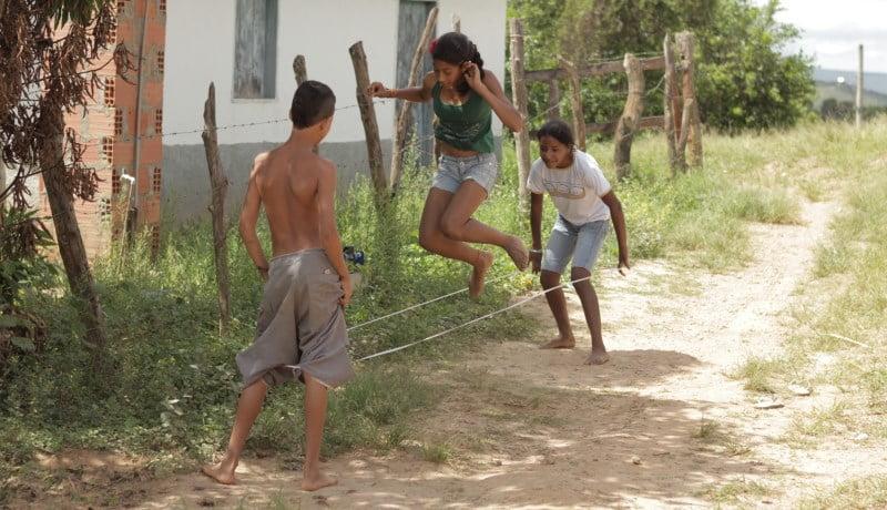 Crianças brincando de elástico em um caminho de terra e mato.