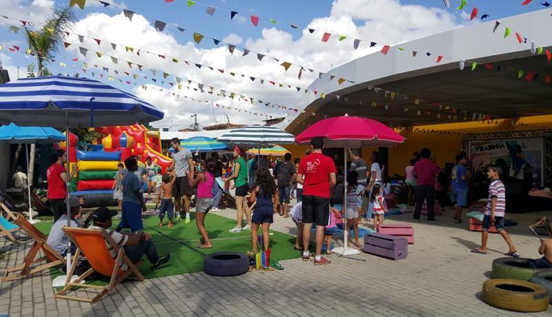 Foto da Viradinha mostra vários adultos e crianças reunidos. Na imagem aparecem vários guarda-sóis e bandeirinhas coloridas