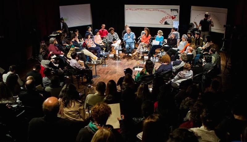 Participantes de evento em roda, debatendo ideias.