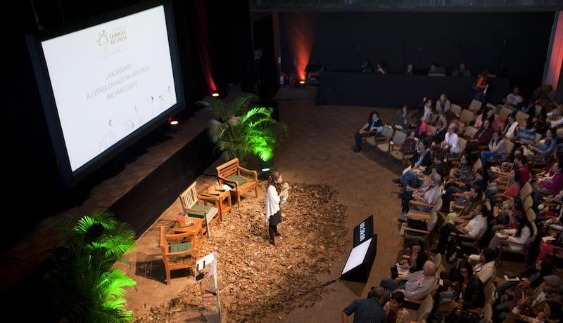 Foto do seminário Criança e Natureza mostra, de ângulo superior, auditório e palestrante.