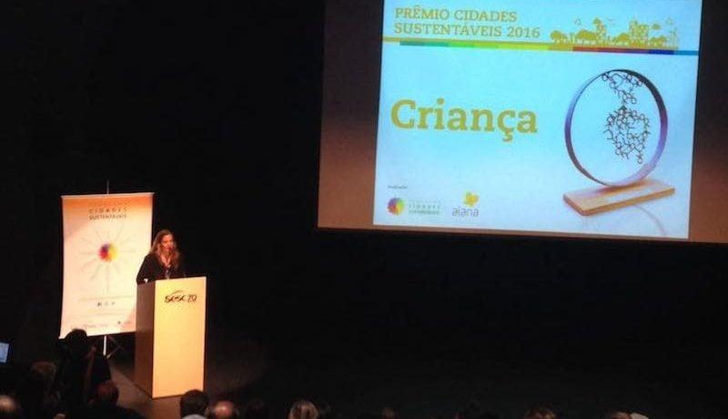 Foto durante Prêmio Cidade da Criança mostra palestrante ao lado de telão