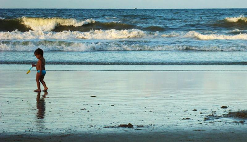 Imagem de uma praia com uma criança parada ao lado esquerdo.