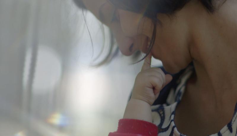 Mulher olhando para o bebe que segura no colo. Uma mãozinha da criança toca seu rosto.