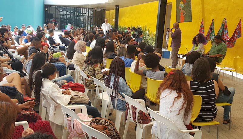 Público do evento que debateu o preconceito racial na atualidade sentado em cadeiras, enquanto um homem fala na frente.
