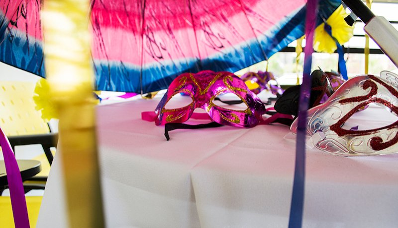 Mesa branca, com várias máscaras coloridas de carnaval