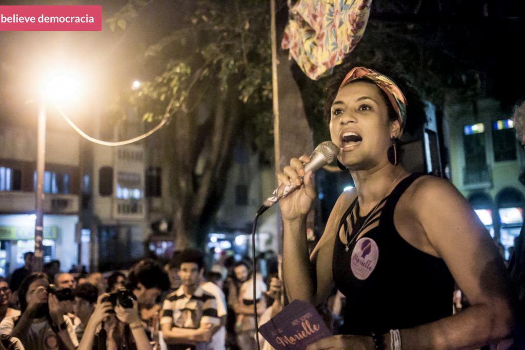 Foto de Marielle Franco falando em microfone