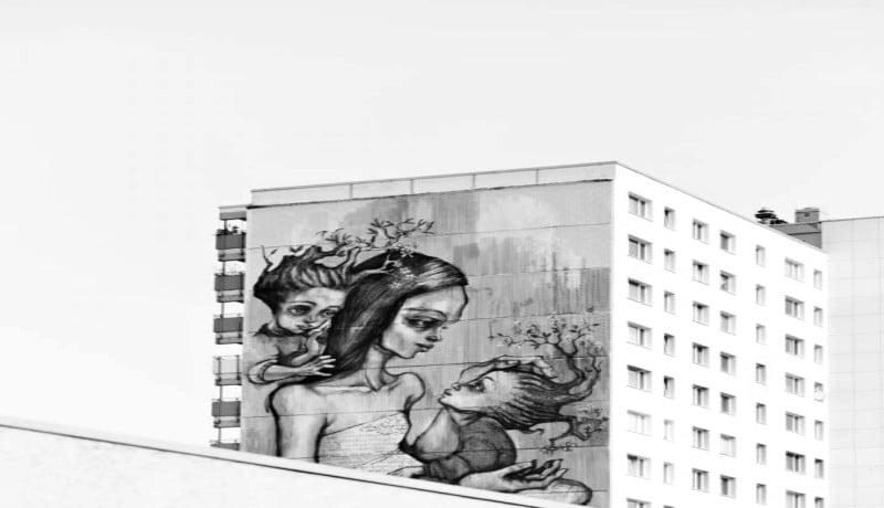 Foto em preto e branco mostra faixada de um prédio ilustrada com uma mulher (que representa a mãe) e duas crianças, uma em seu colo e outra segurando em seus ombros.