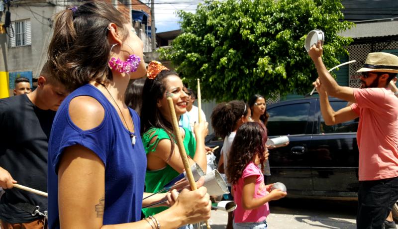 Pessoas se divertindo durante um desfile de carnaval pelas ruas. As duas mulheres que estão em primeiro plano utilizam roupas coloridas (azul e verde) e seguram baquetas em suas mãos.