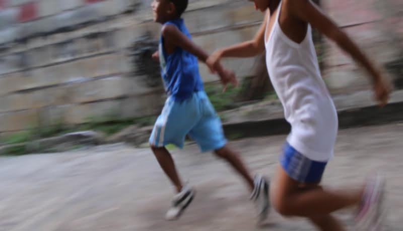 Duas crianças brincam de corrida em uma rua.