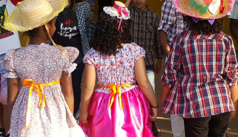 Três crianças aparecem de costas e mãos dadas, vestindo roupas de festa de junina.