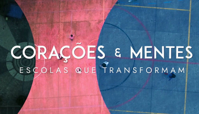 """Fundo de três cores verde, rosa e azul, com letreiro escrito """"Corações e Mentes: Escolas que Transformam""""."""