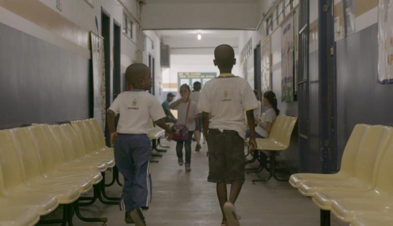 """Foto de uma cena do 2º episódio da série """"Corações e Mentes"""" mostra duas crianças de costas andando em corredor de escola"""