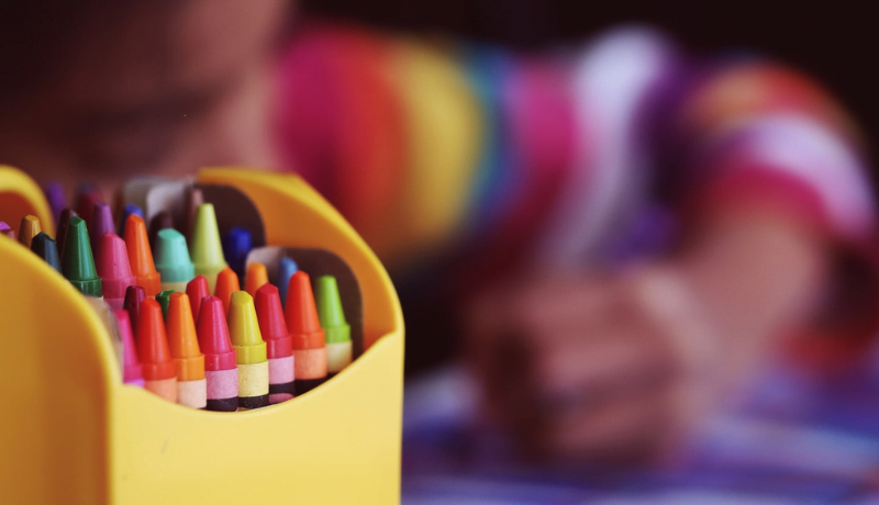 Uma caixa cheia de gizes colorido, e ao fundo uma criança pintando.