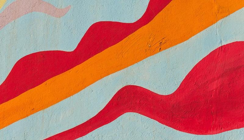 Foto mostra pintura de formas em parede nas cores cinza, laranja e vermelho