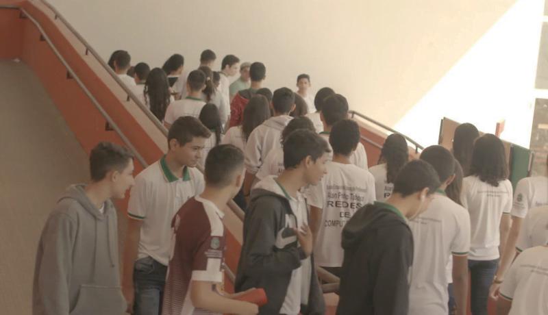 Jovens alunos caminham e sobem as escadas de uma escola.
