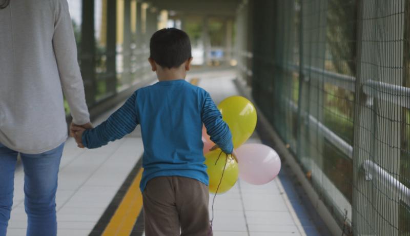 Imagem de um adulto e um menino com bexigas amarelas e rosas na mão. Os dois estão de costas andando por um corredor.