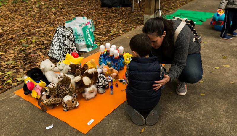 Foto da Feira de Trocas de Brinquedos mostra mãe e criança olhando para um tapete laranja com vários brinquedos